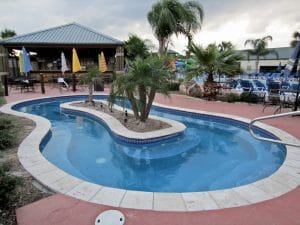 A large, adults-only whirlpool is near one of two tiki bars